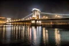 在夜城市的铁锁式桥梁在布达佩斯, Hangury 免版税库存照片