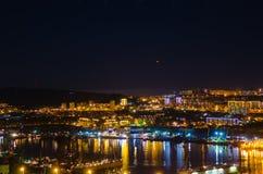 在夜城市符拉迪沃斯托克垂悬的UFO的天空 免版税库存图片