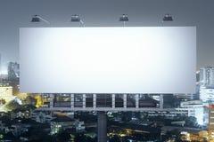 在夜城市背景前面的广告牌 库存照片