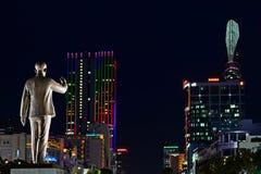 在夜城市背景的胡志明雕象 免版税库存图片