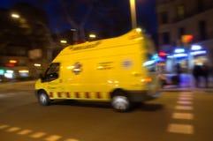 在夜城市街道上的加速的救护车 图库摄影