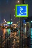 在夜城市街道上的路标地下段落有在多雨天气的水坑的 库存照片