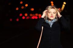 在夜城市街道上的年轻时尚妇女 免版税库存照片