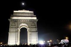 在夜焕发装饰的印度门点燃在印度门德里未认出的人民和游人德里上的12月2日2017年月亮 免版税库存图片