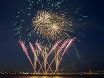 在夜空的多五颜六色的烟花爆炸与光足迹和烟花金黄圈子  免版税图库摄影