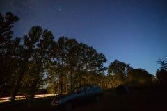 在夜空的星在高速公路在森林里 库存图片