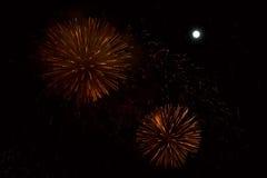 在夜背景的红色和金黄烟花与月亮 免版税库存图片