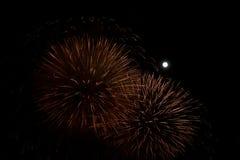 在夜背景的红色和金黄烟花与月亮 图库摄影