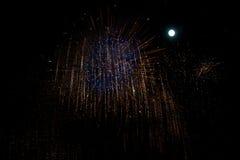 在夜背景的蓝色和红色烟花与月亮 库存照片