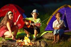 在夜营火附近的愉快的十几岁 免版税库存图片