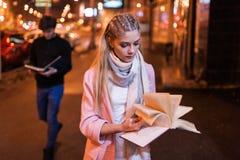 在夜街道上的书痴 有趣读取 图库摄影