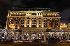 在夜街道上的美妙地发光的大厦 库存照片