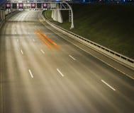 在夜间的速度交通-光在机动车路高速公路落后在晚上 库存图片