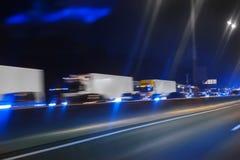在夜高速公路的卡车移动 免版税库存照片