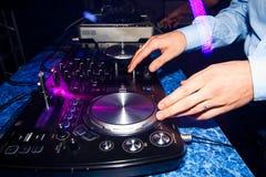 在夜总会棍打在一台搅拌器的DJ混合的音乐 库存照片