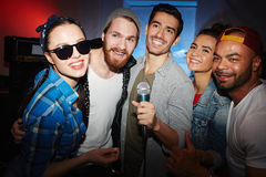 在夜总会的现代党人唱歌卡拉OK演唱 免版税库存图片
