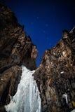 在夜满天星斗的天空的冻瀑布 免版税库存照片