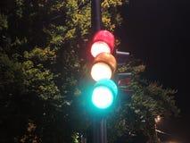 在夜间显示红色,黄色和绿色的红绿灯 免版税库存照片