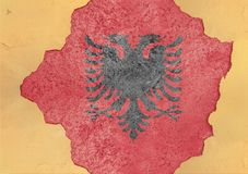 在大具体破裂的孔和残破的材料的阿尔巴尼亚旗子 图库摄影