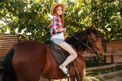 在大农场的快乐的妇女女牛仔骑乘马 免版税图库摄影
