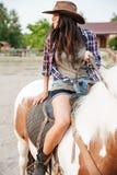 在大农场的愉快的可爱的少妇女牛仔骑乘马 库存照片