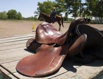 在大农场,被弄脏的背景的马鞍 免版税库存照片