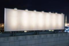 在大厦上面的空白的白色广告牌在夜城市backg的 图库摄影