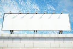 在大厦上面的空白的白色广告牌在蓝天backgro的 免版税库存图片
