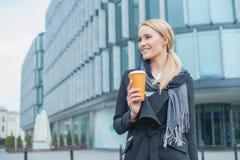 在大厦之外的女实业家用咖啡 库存照片