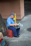 读在大厦之外的老人一张报纸, 免版税库存照片