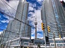 在大厦之间的CN塔在晴天 免版税库存照片