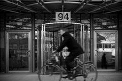 在大厦前面的被弄脏的骑自行车的人 免版税库存照片