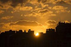在大厦后黑剪影的美好的金黄日落在伊斯坦布尔 免版税库存图片