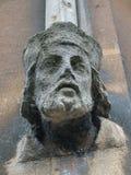 在大厦墙壁上的砂岩雕刻的男性头 免版税库存照片
