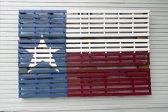 在大厦墙壁上绘在木板台和挂的得克萨斯旗子 免版税库存图片