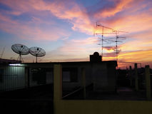在大厦屋顶的抛物面卫星盘 免版税库存照片