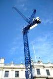 在大厦旁边的蓝色起重机塔 库存图片