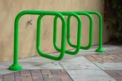 在大厦旁边的螺旋金属管自行车行李架 免版税库存图片