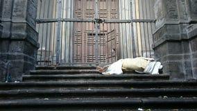 在大厦的台阶的睡觉的粗砺的无家可归者在门前面的 图库摄影