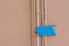 在大厦的墙壁上的蓝色箭头 库存照片