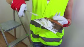 在大厦的妇女建筑工人研的墙壁 股票视频
