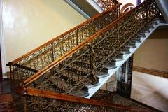 在大厦的旁边楼梯与木扶手栏杆和伪造的操刀 免版税库存图片