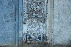 在大厦的混凝土墙上的老被摩擦的肮脏的门 库存图片