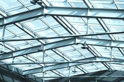 在大厦的玻璃屋顶,在屋顶下 现代办公楼的玻璃和金属建筑与外部蓝天的 免版税图库摄影