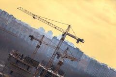 在大厦的建筑用起重机反对黄色天空 免版税库存照片