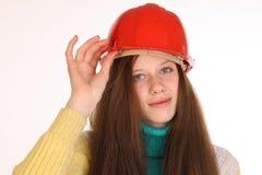 在大厦盔甲的女孩可笑的建造者 库存照片