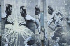 在大厦石墙上的街道画运动员  免版税库存照片