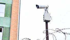 在大厦背景的照相机录影监视在砖墙登上了,操刀与铁丝网 免版税库存照片