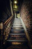 在大厦里面的老木楼梯 免版税库存照片