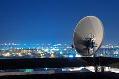 在大厦顶部的卫星盘天线在晚上 免版税库存照片